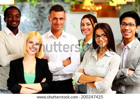 Happy group of co-workers standing in office - stock photo