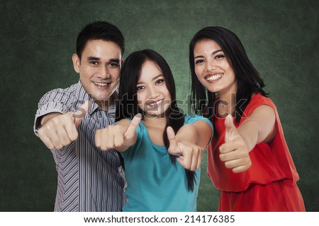 Happy group of college students, showing thumbs-up at camera
