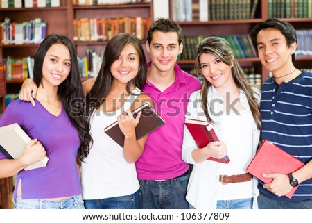 Happy group of college students smiling at the library - stock photo