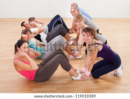 Happy group of diverse people full of health and vitality working out in a gym strengthening abdominal muscles doing head lifting - stock photo
