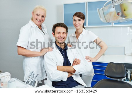 Happy group of employees at dentist with two dental assistants - stock photo