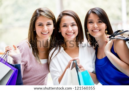 Happy group of female friends shopping holding bags - stock photo