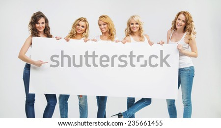 Happy group of female friends with empty board - stock photo