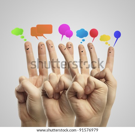 Happy group of finger smileys with social chat sign and speech bubbles. Fingers representing a social network. - stock photo