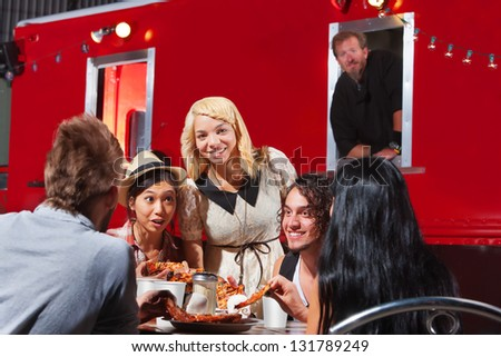 Happy group of friends eating out by food truck