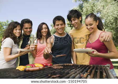 Happy group of friends gathered around grill at picnic - stock photo