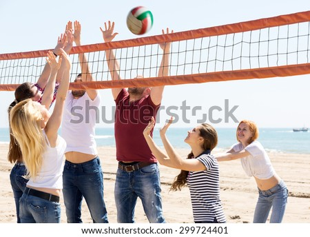 happy group of friends having fun at beach and playing ball  - stock photo