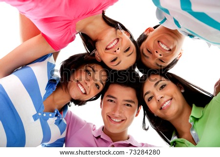 Happy group of friends hugging and smiling � isolated over white