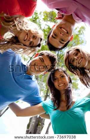 Happy group of friends hugging and smiling outdoors - stock photo