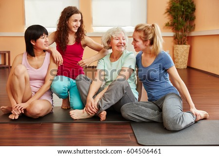 Happy group of friends in yoga class break talking with each other