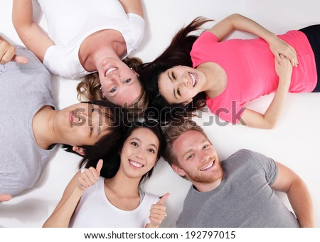 Happy Group of friends lying and making a circle, asian and caucasian - stock photo