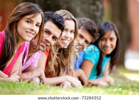 Happy group of friends lying on the floor outdoors - stock photo