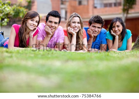 Happy group of friends lying on the floor outdoors