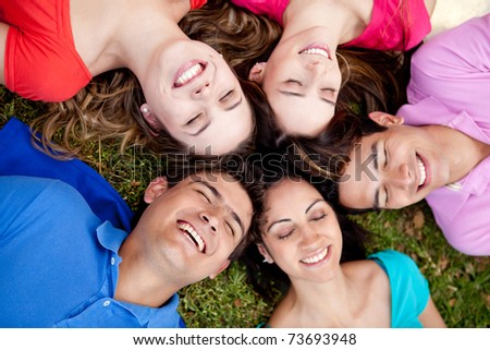 Happy group of friends lying on the floor with eyes closed
