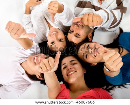 Happy group of friends lying on the floor with thumbs up isolated on white - stock photo