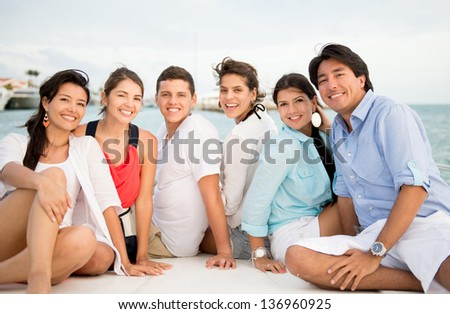 Happy group of friends on a boat enjoying the summer - stock photo
