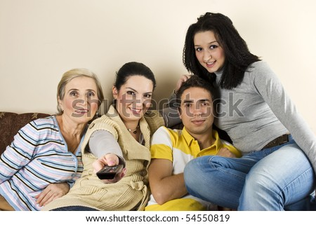 Happy group of friends or family watching tv and smiling - stock photo