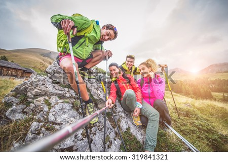 Happy group of friends photographing themselves  - Hikers on excursion in the nature having fun and taking a selfie with action camera stick - stock photo