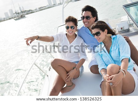 Happy group of friends sailing on a boat and pointing away - stock photo