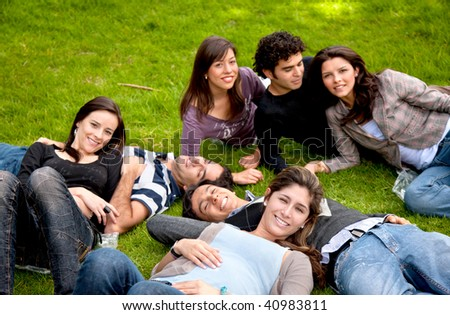 happy group of friends smiling and lying on the grass outdoors