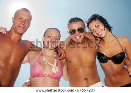 Happy group of friends smiling at the beach - stock photo