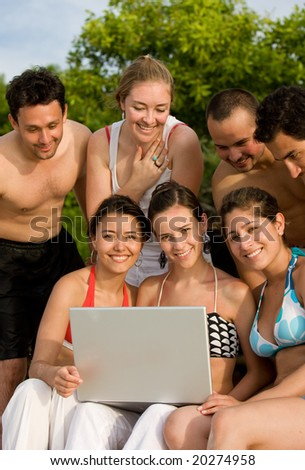 Happy group of friends smiling at the beach with a laptop computer