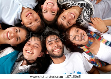 happy group of friends smiling with their heads together on the floor