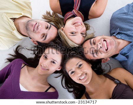 happy group of friends smiling with their heads together on the floor isolated