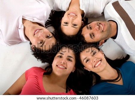 Happy group of friends together lying on the floor isolated on white