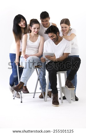 Happy group of friends using Tablet PC device. Mixed race group. Isolated on a white background. - stock photo