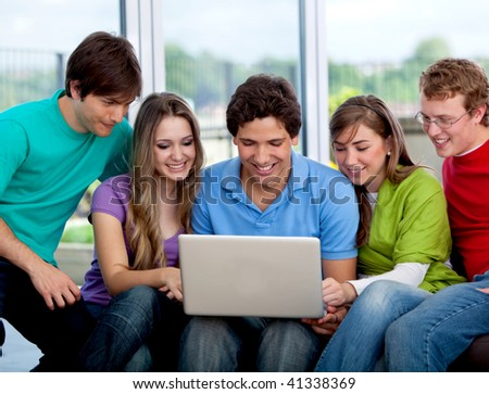 Happy group of friends with a laptop