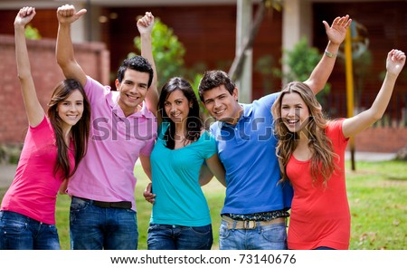 Happy group of friends with arms up outdoors