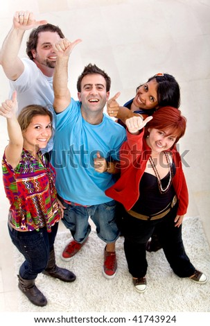 Happy group of friends with thumbs and arms up indoors