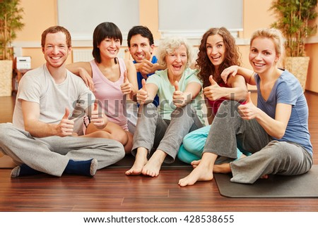Happy group of friends with thumbs up in pilates class - stock photo