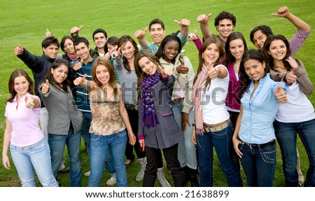 happy group of friends with thumbs up outdoors in a park - stock photo