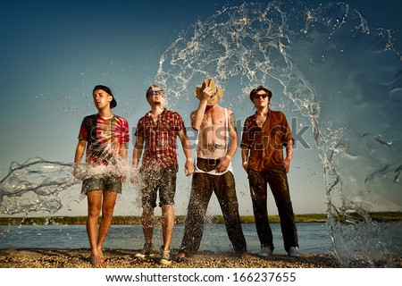 Happy group of friends with water splash at the beach  - stock photo