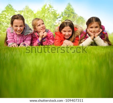 Happy group of girls lying on a green grass - stock photo