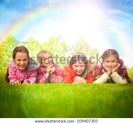 Happy group of girls lying on a green grass. Rainbow and sun overhead - stock photo