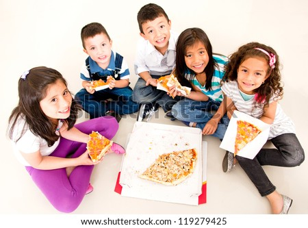 Happy group of kids eating pizza and smiling - stock photo