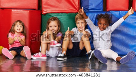Happy group of kids in preschool gym holding their thumbs up - stock photo