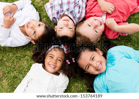 Happy group of kids lying on the floor in a circle  - stock photo