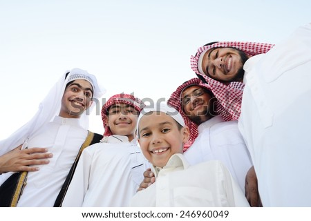 Happy group of Middle eastern Gulf boys standing in row line - stock photo