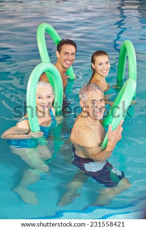 Happy group of people in aqua fitness class in swimming pool - stock photo