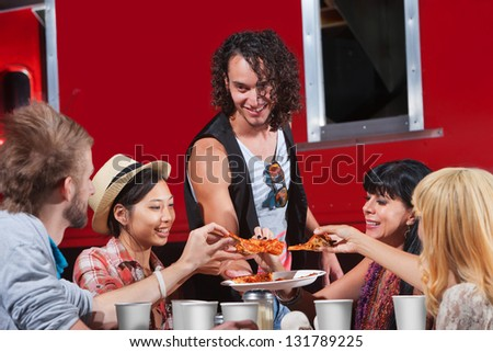 Happy group of people sharing slices of pizza