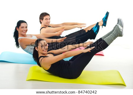 Happy group of people stretching their hands and legs and sitting on colorful mats - stock photo