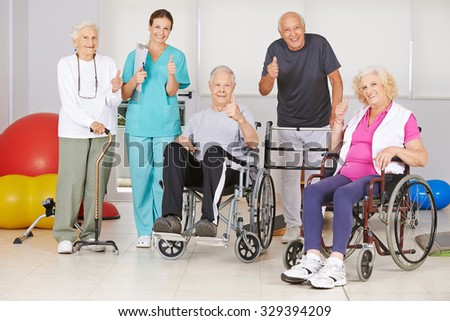 Happy group of senior people and nurse holding thumbs up in physiotherapy - stock photo