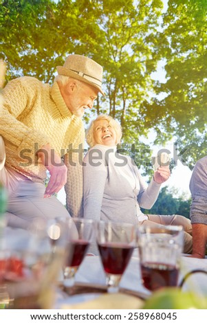 Happy group of senior people playing cards in summer in a park - stock photo
