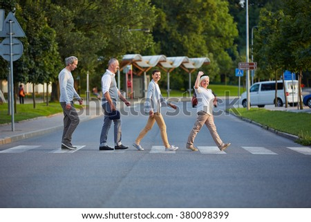 Happy group of seniors walking over crosswalk in a line - stock photo