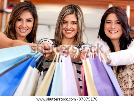 Happy group of shopping women holding bags at a store