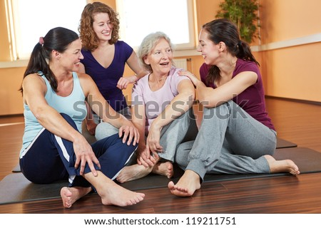 Happy group of smiling woman talking in a fitness center - stock photo